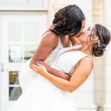 Black womxn (L)dipping and kissing white womxn (R) - both in wedding dresses