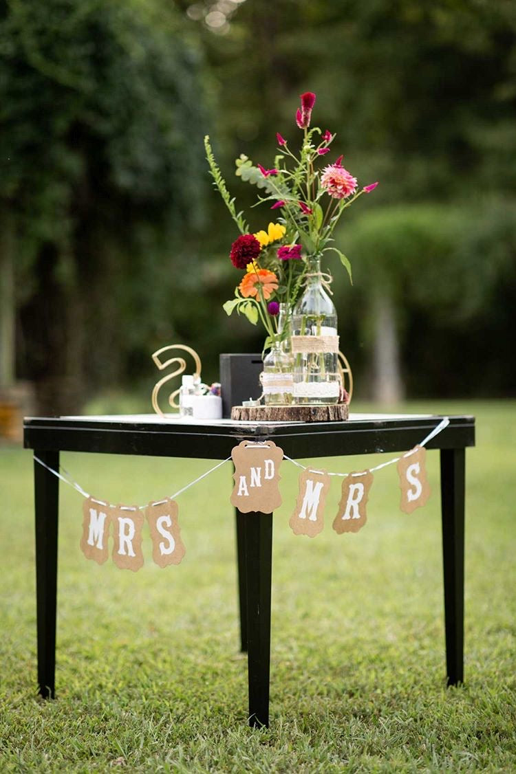 Mrs and Mrs Brown Craft Banner Hanging from a Black Table Decorated with Flowers