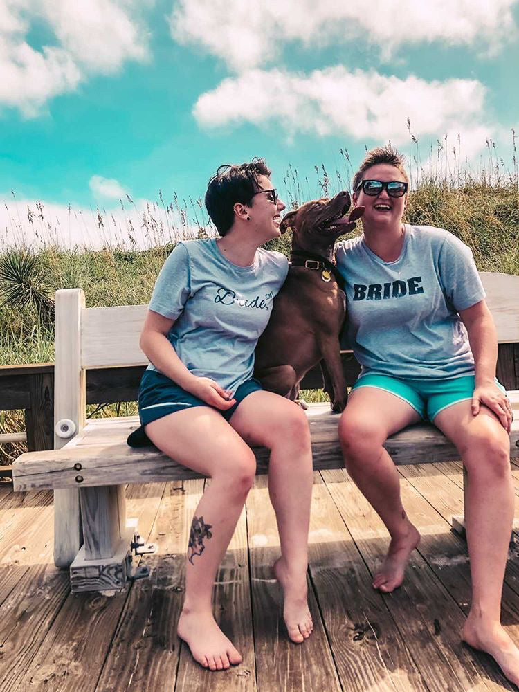 Two People Wearing Grey Bride Tees on a Bench at the Beach with a Dog