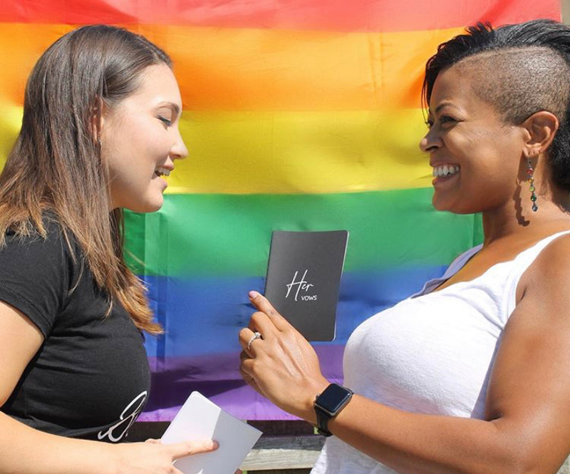 Two People Smiling at Each Other Holding Black and White Her Vow Books in Front of Rainbow Pride Flag