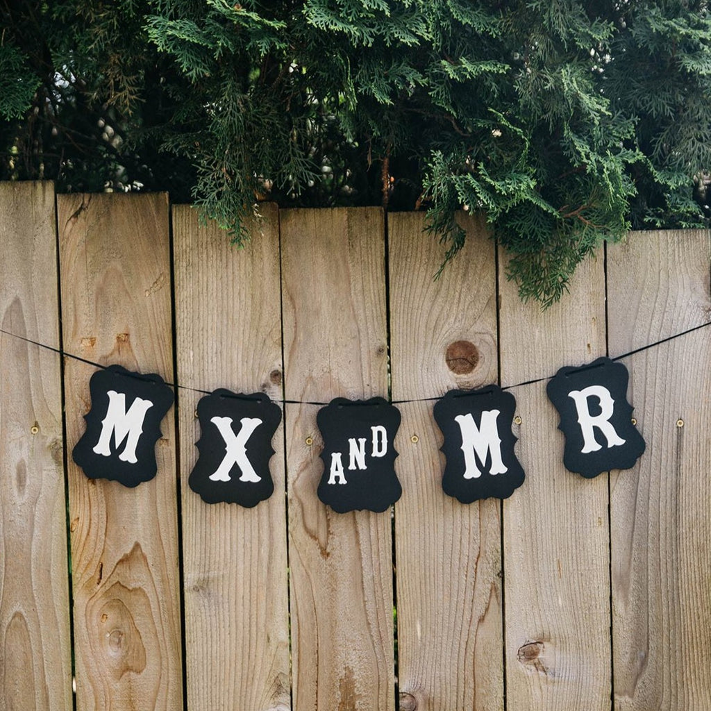 Mx and Mr Black Craft Banner Hanging from Wooden Fence