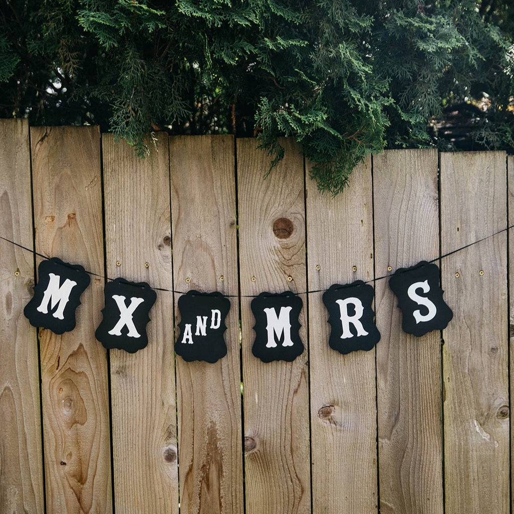 Non-Binary Mx and Mrs Black Craft Banner Mx and Mr Black Craft Banner Hanging from Wooden Fence