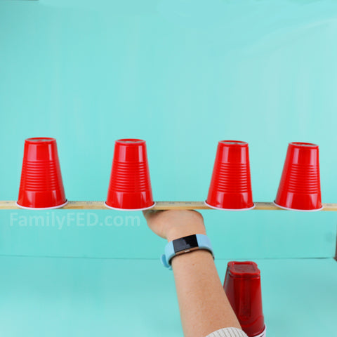 Balance the yardstick and cups on the back of your hand.