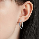 Sapphire and Cubic Zirconia Oval Hoop Earrings  in Sterling Silver on young model