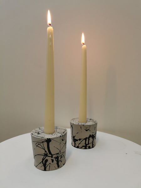 Custom designed candlestick holders made of concrete with black paint scribbled on it