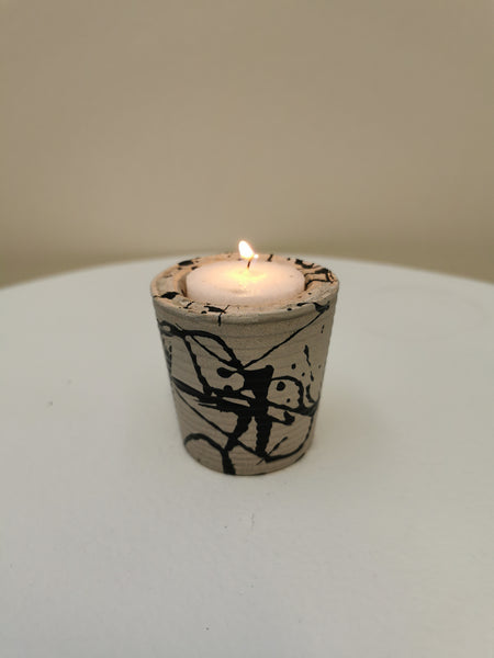 Custom designed tea light holder made of concrete with black paint scribbled on it