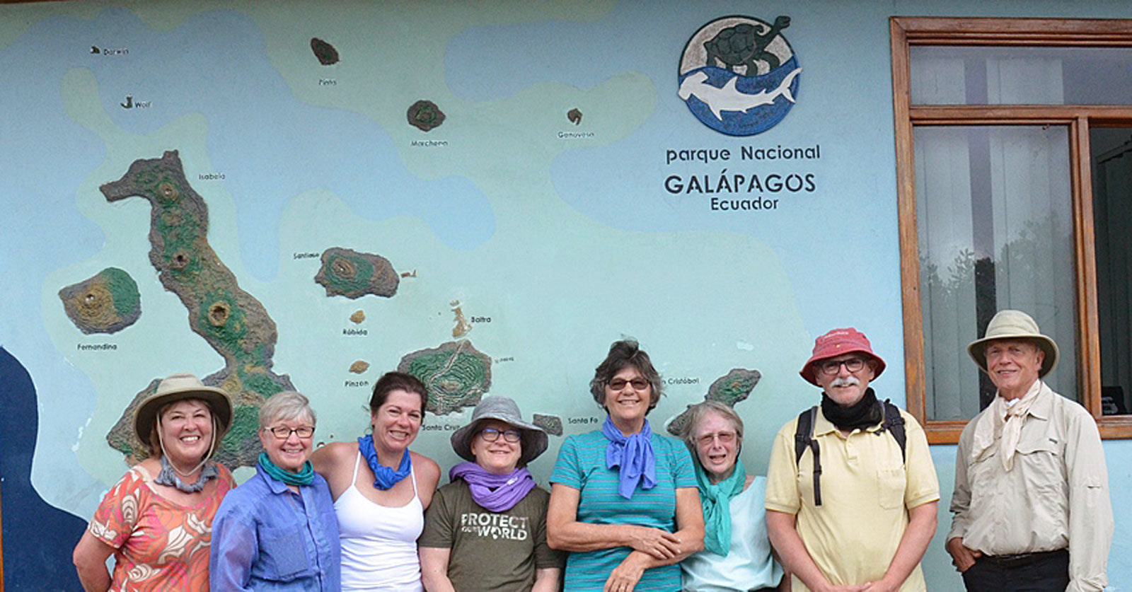a group of men and women standing against a map of the Galpagos wearing WrapMeCools