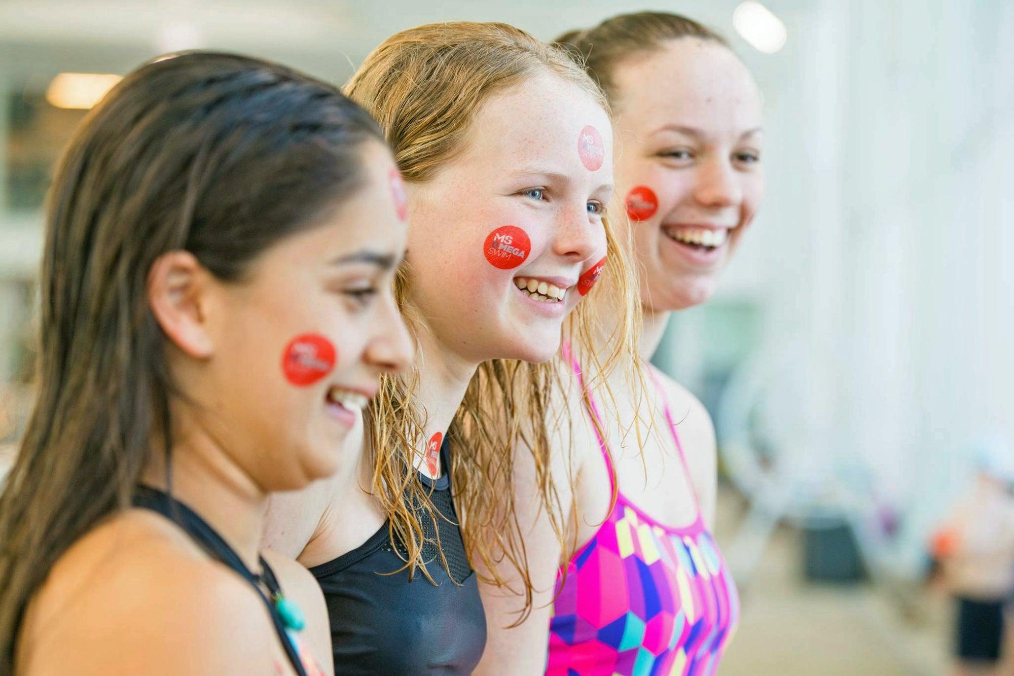 3 young women smiling as they are about to enter the pool