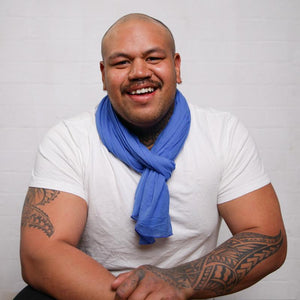 male with tattoos wearing cornflower blue neck scarf