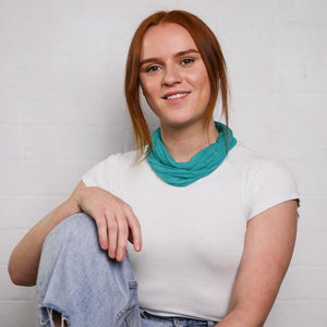 red-haired female with white T-shirt and medium sea green neck scarf