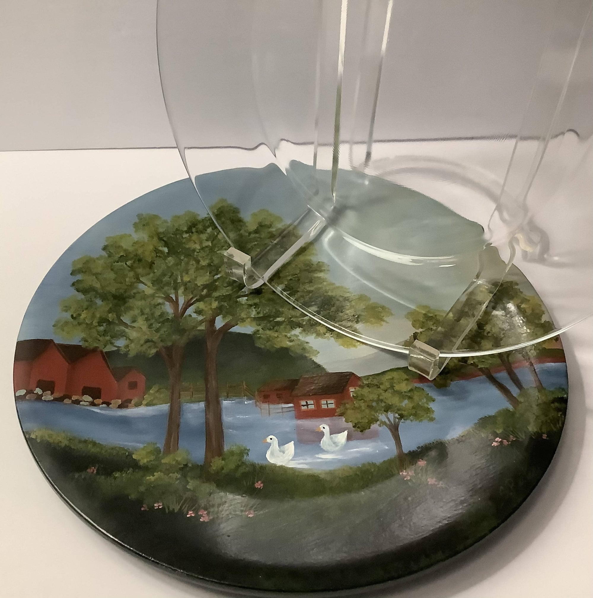 A Round Hand Painted Charger Plate with a Folk Art Scene of Cottages, Lake and Swans - a Clear Glass Plate is Included