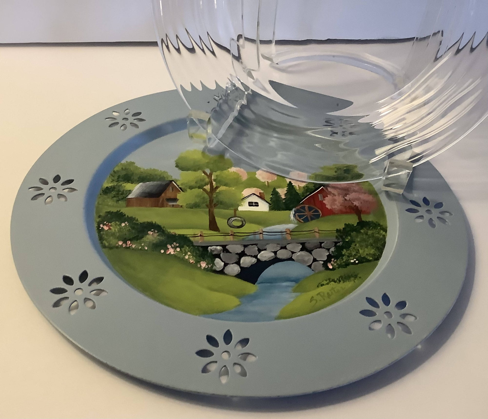 A Small Round Charger Metal Plate With a Hand Painted Picture of a Village and Stone Bridge in Spring - Clear Glass Plate Included