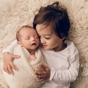 Peta Nikel Hobart Newborn Photographer Sibling portrait with older child and newborn baby on flokati rug