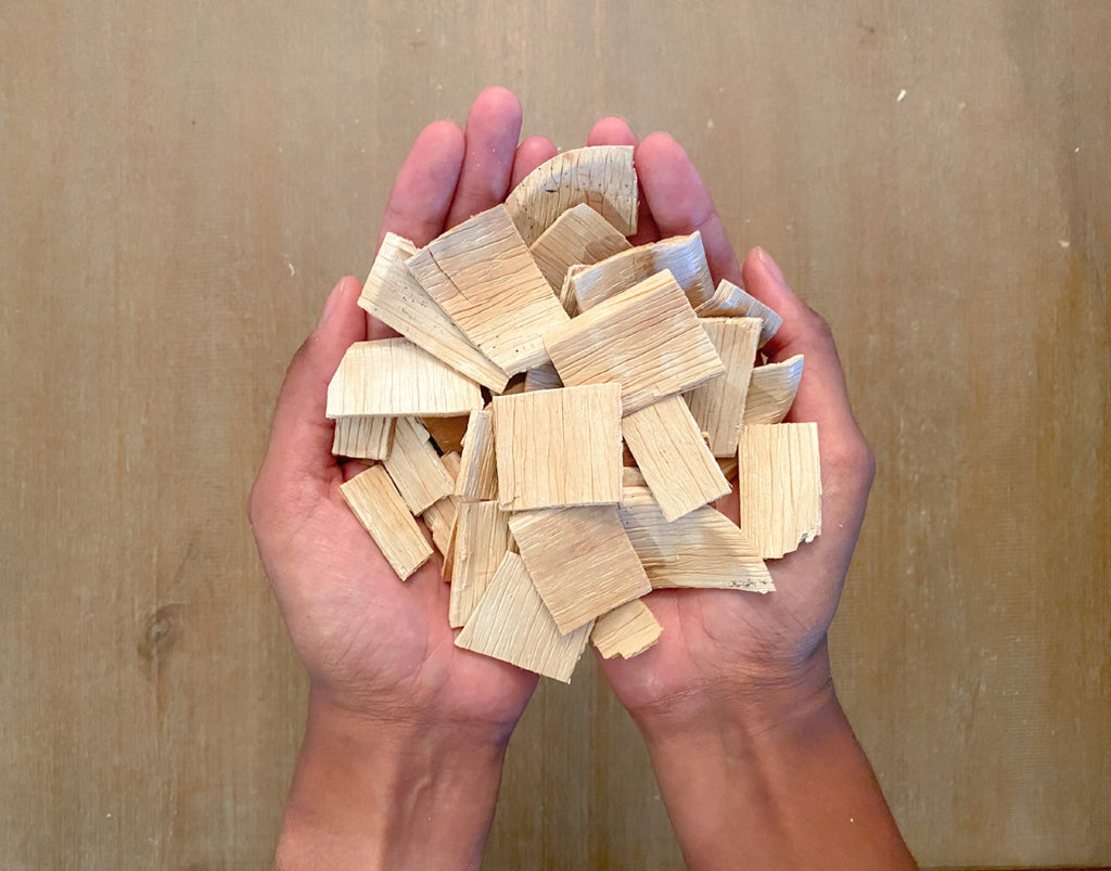 hands holding pieces of palm leaf plates