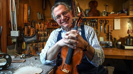 Master Violin Maker Charles Rufino posing with violin in his shop