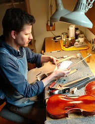 Endre setting the neck on his new violin