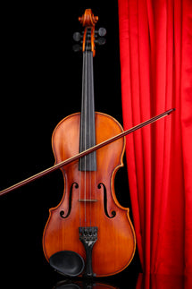 Violin in front of a red stage curtain