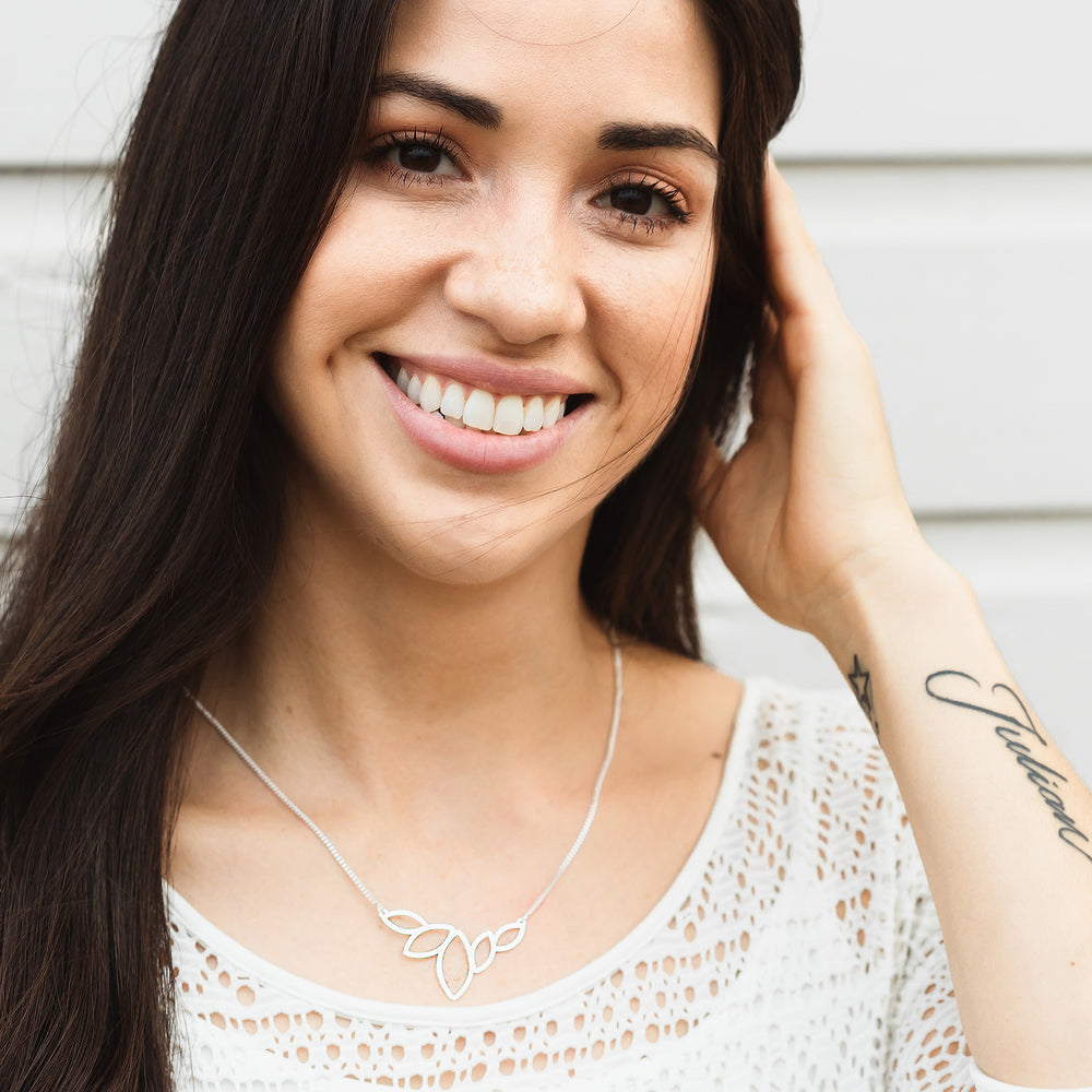 Silver Lotus charm necklace on a model - statement necklace