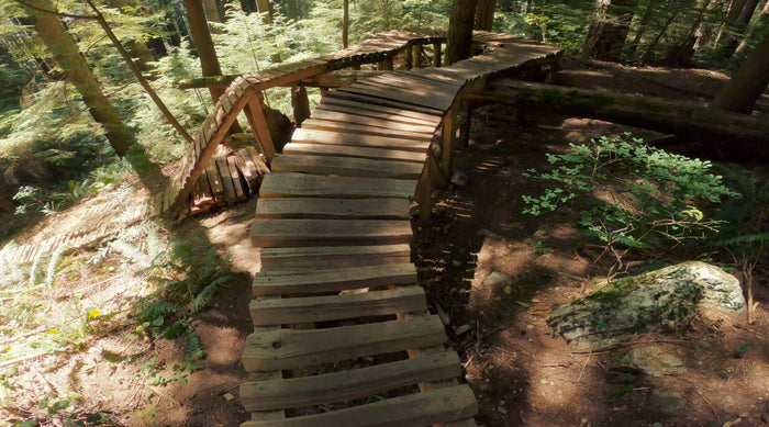 Header image for Pick A Part How to Ride Ladder Bridges article. Image is a wooden ladder mountain bike trail feature.