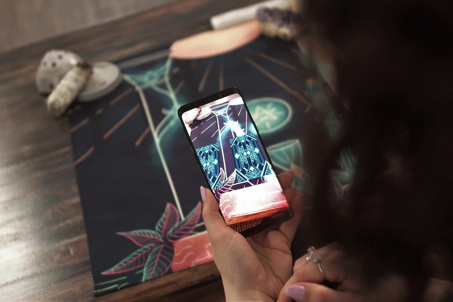 Woman holding a phone to use augmented reality to show a tarot spread