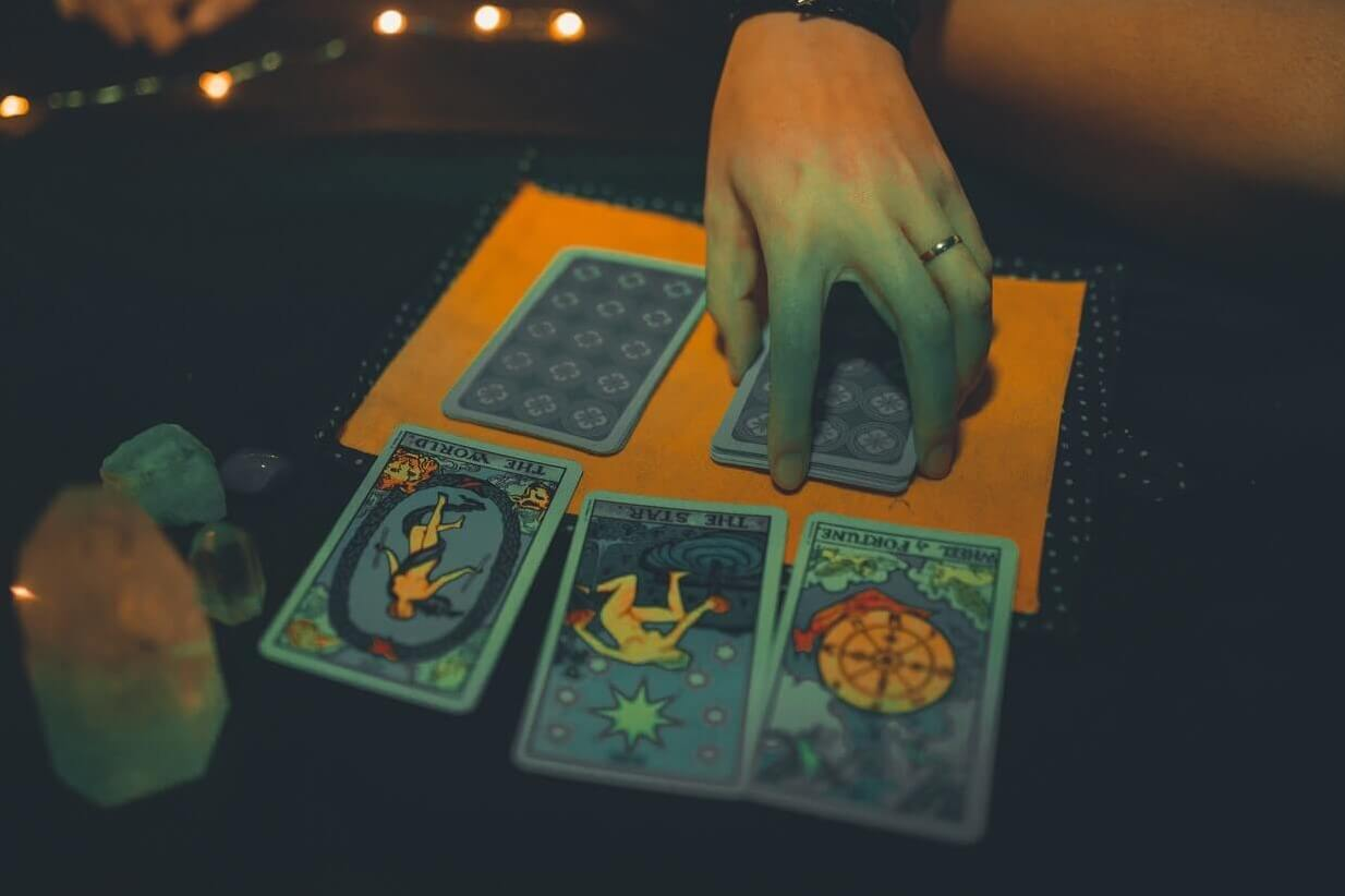 Person drawing three cards to YES NO tarot reading