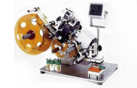 Semi-automatic tamp labeler for short production runs of flats or ovals, or for difficult to handle parts, model CVC 120, by Acasi Machinery Inc.