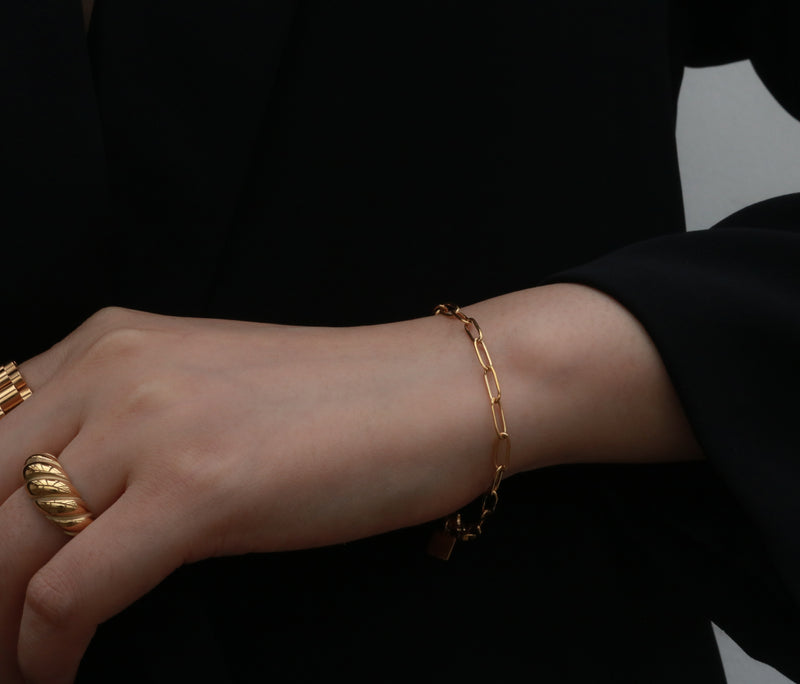 Women wearing gold rings and a link chain bracelet