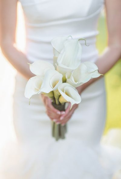 A formal posy of elegant white calla lilies created by Clarendon Hills