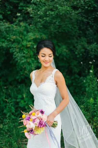 A vision in white with a neat updo beautifully highlighted with sheer veil