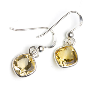 Diamond-shaped citrine silver drop earrings on white background
