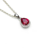 Lab ruby teardrop Pendant with cz halo sterling silver on white background