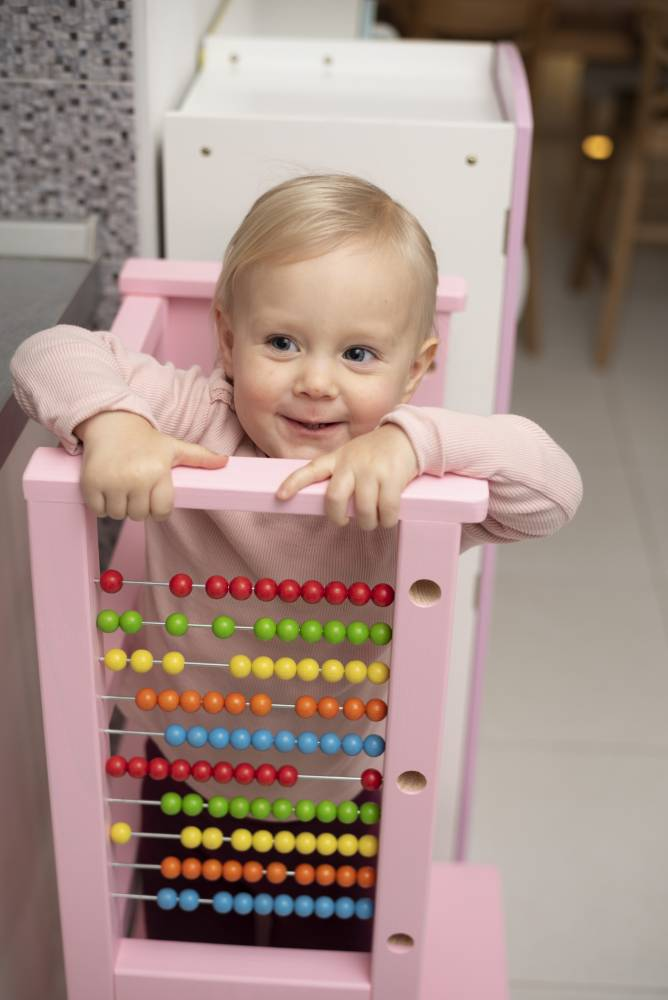 Child playing with an abacus on a learning tower