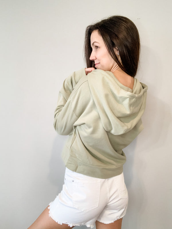 This midweight hoodie is the perfect sweatshirt for spring and summer, and we are loving this sage green color! Features a shoulder cut-out detail, hood with dip-dyed drawcords, and is slightly cropped to hit the top of your shorts or pants. Fits true to size.