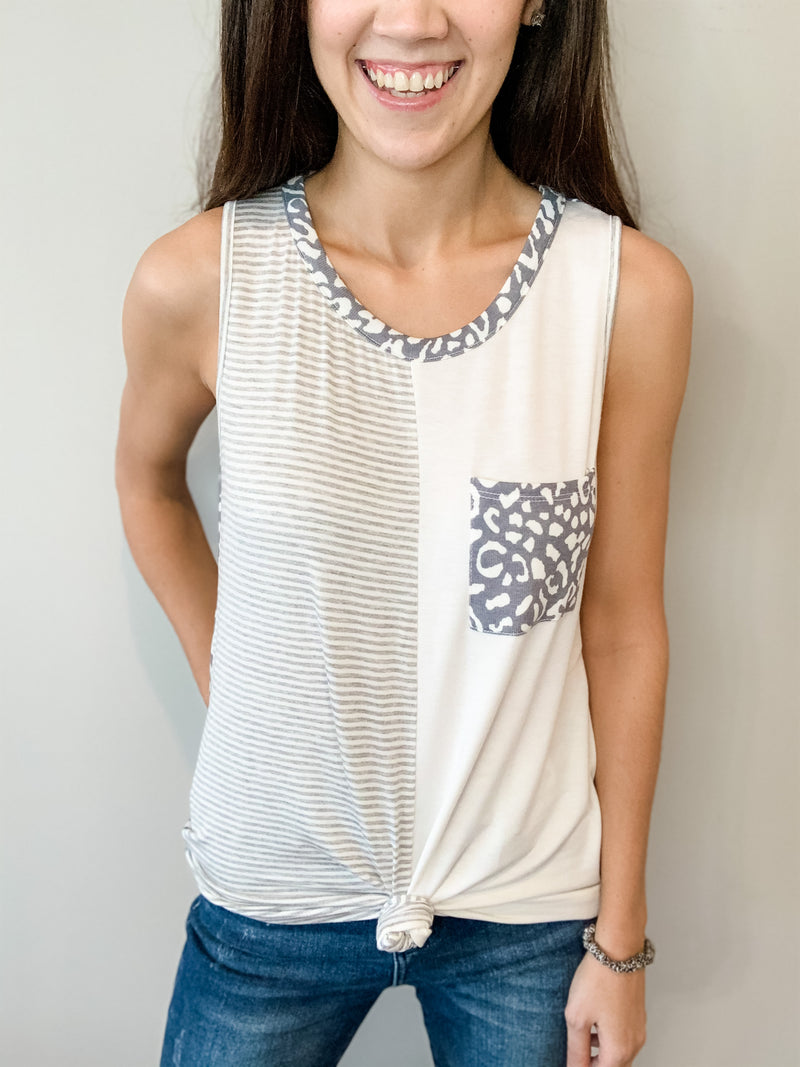 This adorable tank top is super soft and stretchy with a comfortable flowy fit and front pocket. Features fun, color blocking details with white, grey stripes, and navy leopard. Tie in the front for a cute, easy look!