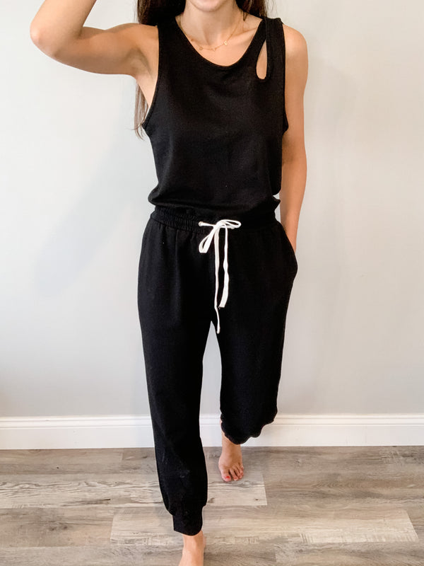 This black jumpsuit is your new closet staple! Features shoulder cut-outs, a back keyhole, adjustable drawstring waist, and jogger cuff. Fits true to size.