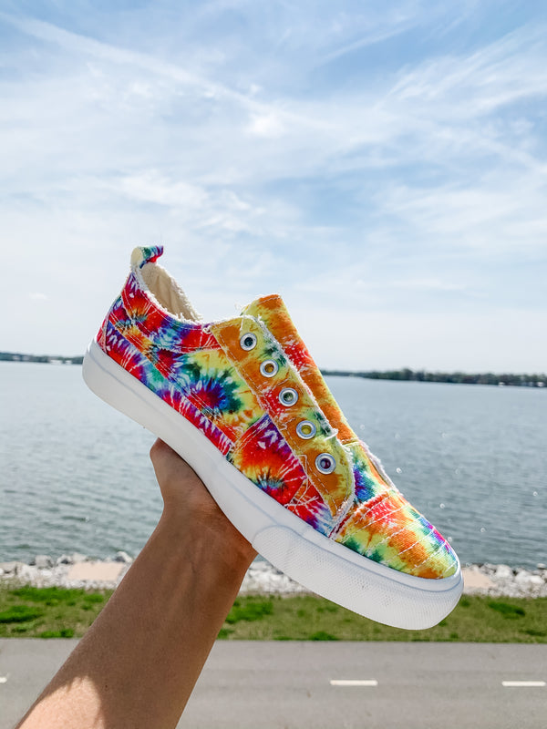 "These rainbow tie dye slip-on sneakers are PERFECT for summer with your favorite pair of jean shorts or even a casual black dress. When you see ""Corkys"" you KNOW they are going to be comfortable, too!  Sizing: Available in whole sizes only - if you are between sizes, please SIZE UP. Megan is between sizes 8-8.5 and wears the 9 in Corkys!"