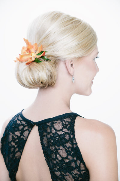 A romantic low bun accented by a floral detail. | Floral Headpiece Inspiration for Brides & Bridesmaids | Kennedy Blue