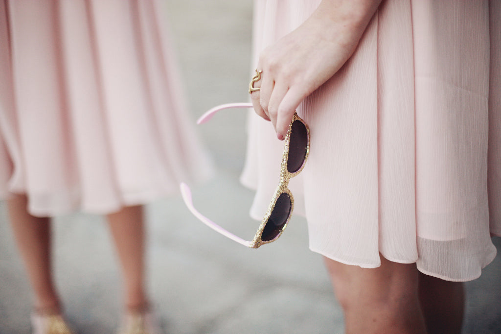 Blush pink bridesmaid dresses with gold, glitter sunglasses. | A Whimsical Gold and Pink Wedding Day