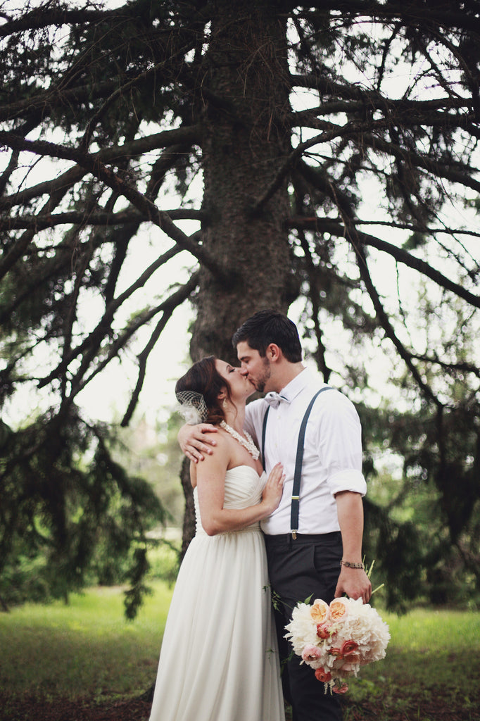 A bride in along, chiffon wedding dress and a groom in suspenders is the perfect, rustic combination! | A Whimsical Gold and Pink Wedding Day