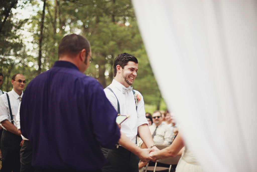 A fun shot of the happy groom from the outdoor wedding ceremony. | A Whimsical Gold and Pink Wedding Day