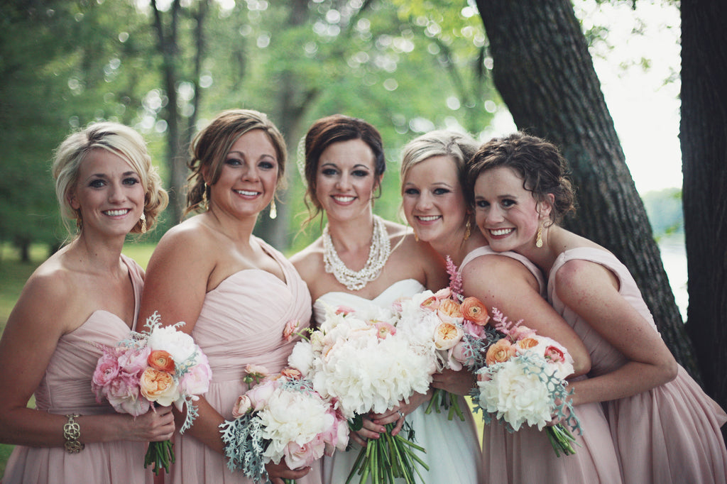 The bridal party wore gorgeous one-shoulder, chiffon bridesmaid dresses in blush. | A Whimsical Gold and Pink Wedding Day