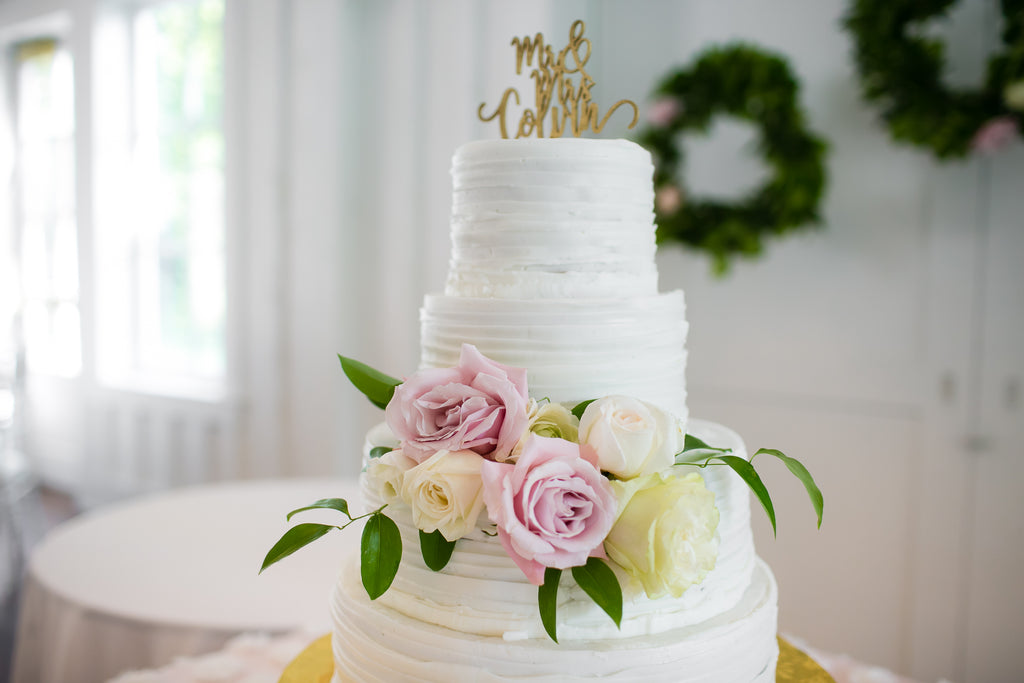 The wedding cake featuring blush accents.