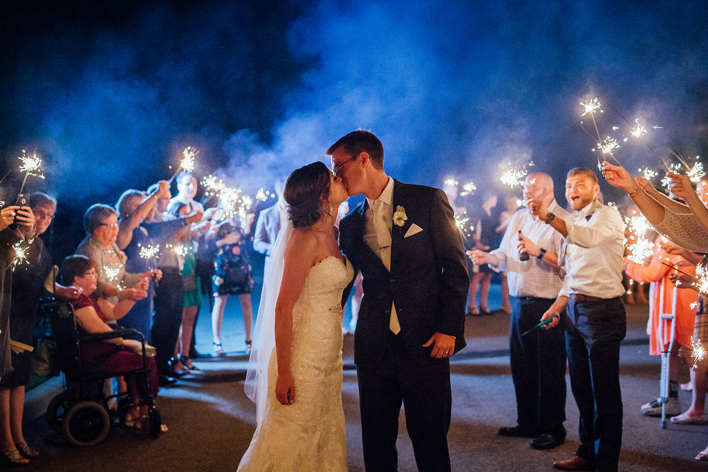 The bride and grooms kiss during their send off! | A Simple & Stunning Sage Wedding | Kennedy Blue | Rachel Figueroa Photography