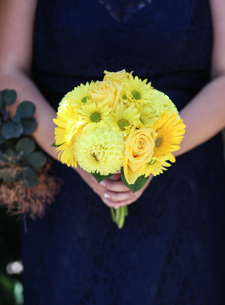 Give your girls a pop of color with a yellow bridesmaids bouquet. See all of the details from Jenna and Nate's rustic wedding in Wisconsin. | A Charming Blue and Yellow Wedding