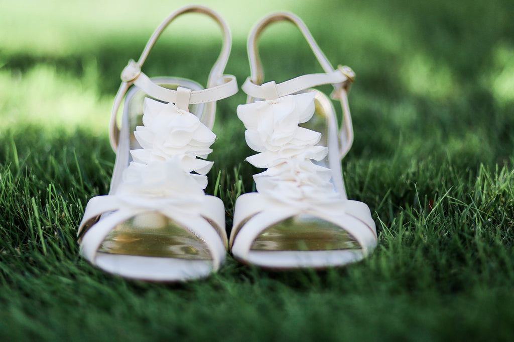 These white bridal shoes are perfect for a summer wedding. See all of the details from Jenna and Nate's rustic wedding in Wisconsin. | A Charming Blue and Yellow Wedding