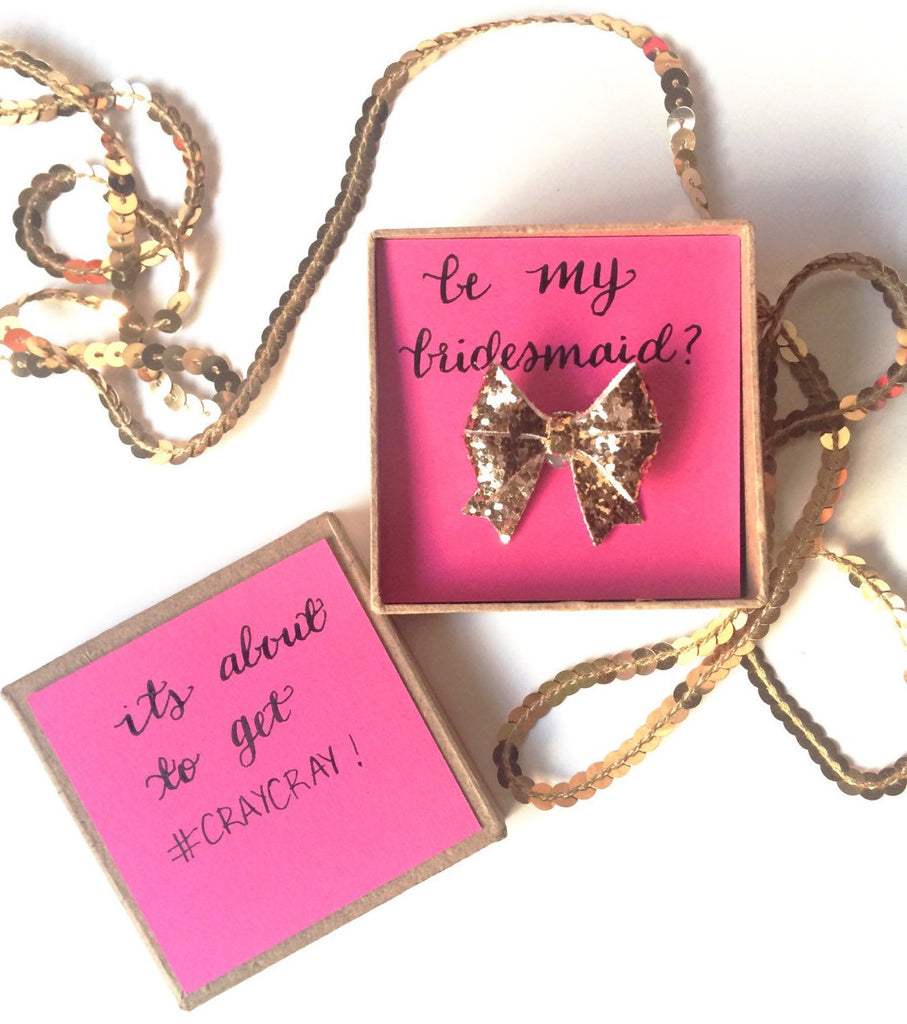'Will you be my bridesmaid?' glitter bow ring and box. | The Ultimate List of Bridesmaid Proposal Ideas - 25 Creative Ways to ask Your Bridesmaids