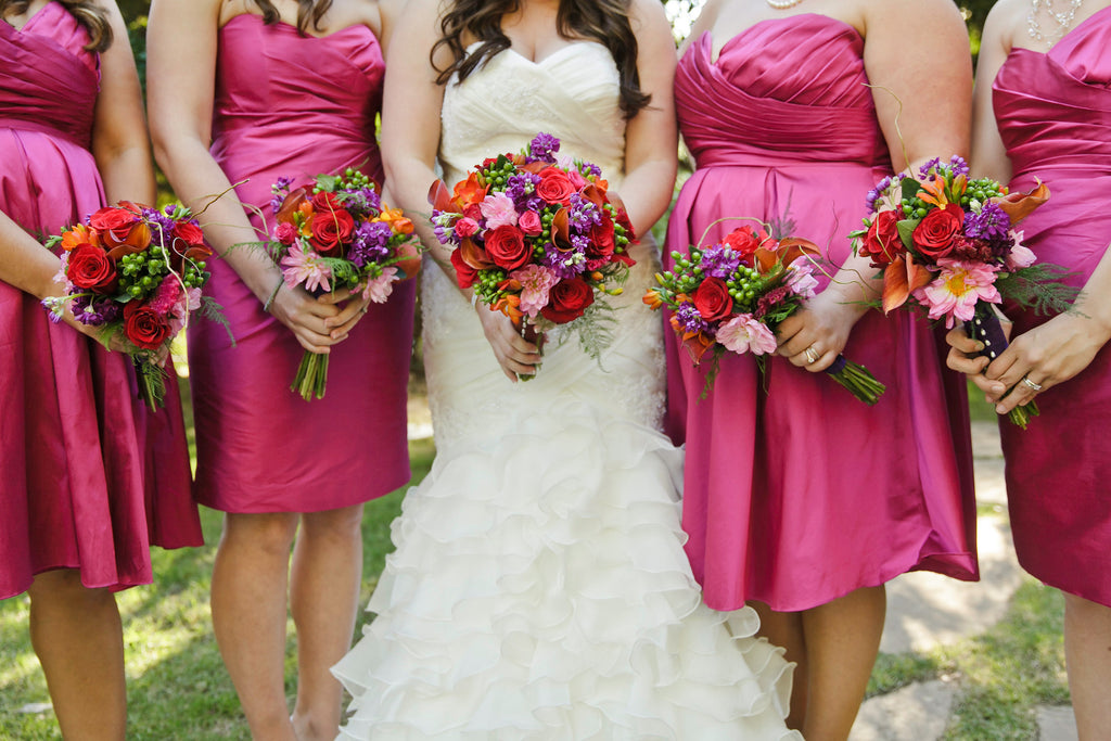 Pink bridesmaid dresses add a fun pop of color for a Halloween-themed wedding.