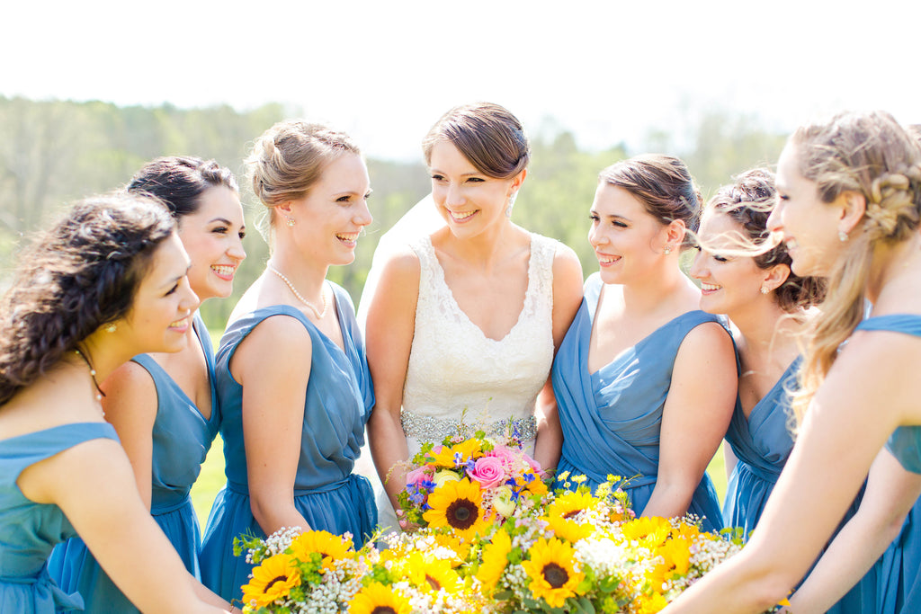 Cute photo of the bride and her bridesmaids gathering around their colorful bouquets! | 26 Photos To Take With Your 'Maids | Kennedy Blue | Emily Sacra Photography