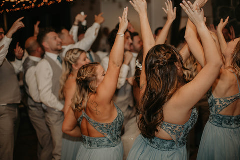 Bridesmaids and Groomsmen waving their hands in the air as they dance to a song.