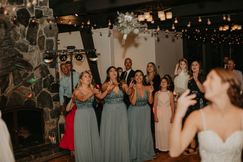 Bride looking over her shoulder as she tosses her bouquet to a crowd of women.